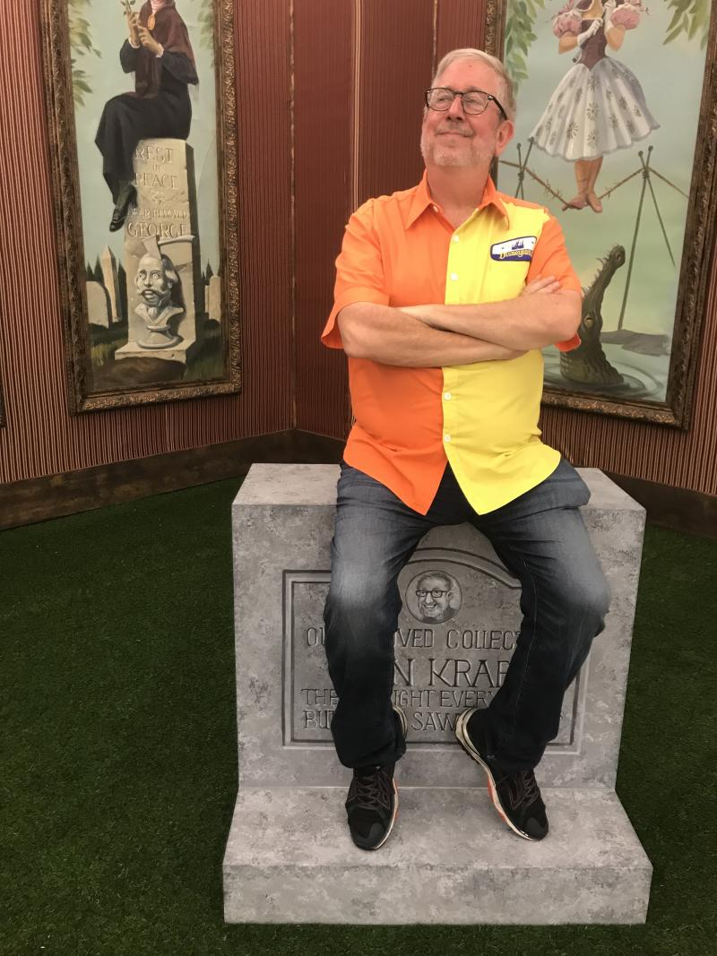Disney Collector poses in front of a personalized tombstone, just like the ones outside the Haunted Mansion. (Photo: Yahoo Entertainment)