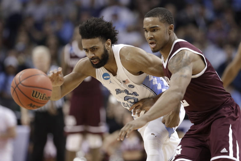 North Carolina's Joel Berry II, left, and Texas A&M's TJ Starks, right, chase the ball during the second half of a second-round game in the NCAA men's college basketball tournament in Charlotte, N.C., Sunday, March 18, 2018. (AP Photo/Gerry Broome)