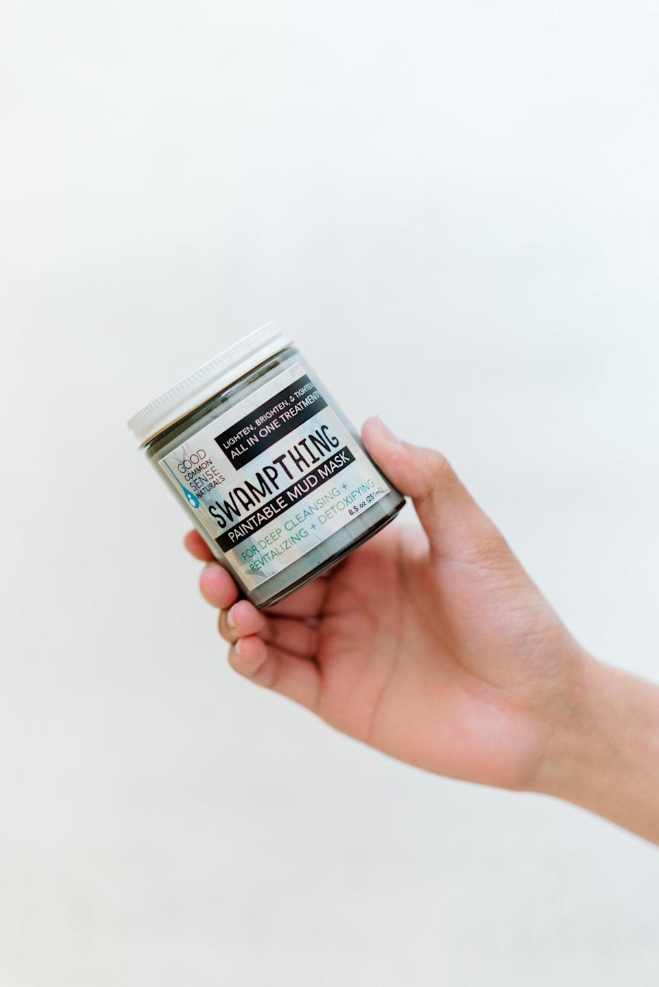 hand holding jar of charcoal mud face mask