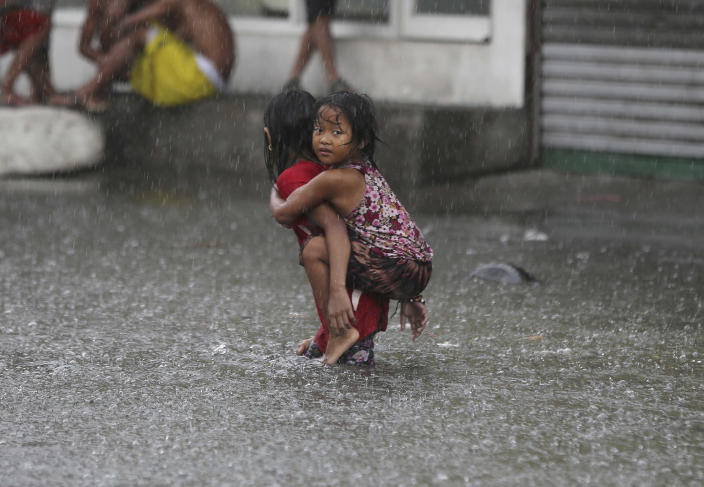 <p>A Filipino girl is carried along a flooded road in suburban Mandaluyong, east of Manila, Philippines, as monsoon downpours intensify while Typhoon Nepartak exits the country, July 8, 2016. (Photo: Aaron Favila/AP) </p>