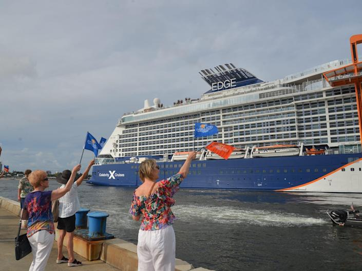 Crowds waving Port Everglades flags at the departing Celebrity Edge.
