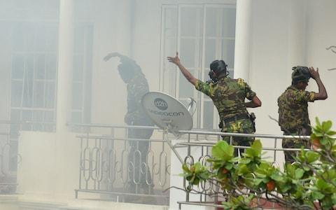 Sri Lankan Special Task Force (STF) personnel gesture outside a house during a raid - Credit: ISHARA S. KODIKARA/AFP