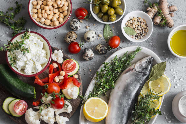 Mediterranean style food background. Fish, vegetables, herbs, chickpeas, olives, cheese on grey background, top view. Healthy food concept. Flat lay