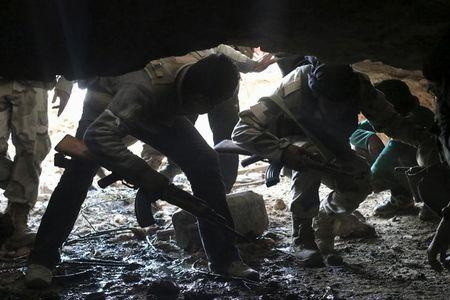 Free Syrian Army fighters enter a cave after what they said was a barrel bomb dropped by forces loyal to Assad near Tal Meleh village in Hama countryside