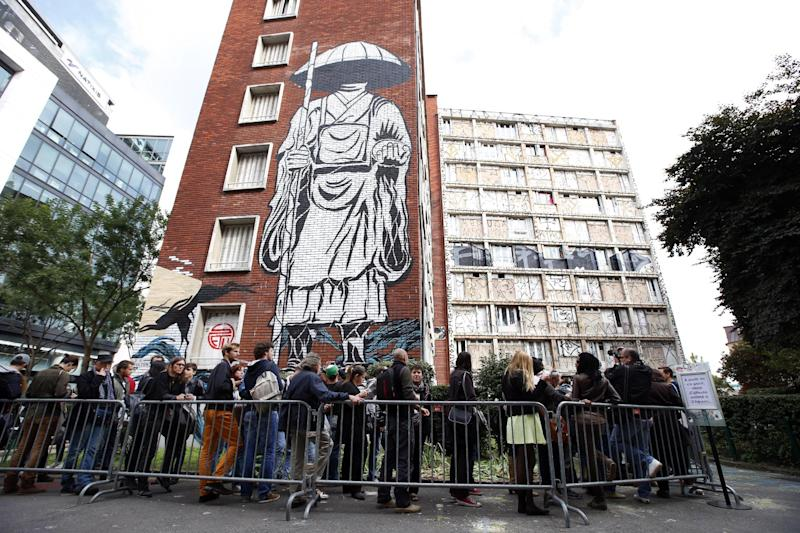 People queue to visit a social housing tower converted into a temporary street art exhibition in Paris, France, Tuesday, Oct. 8, 2013. Condemned apartments never looked so good _ and only rarely has graffiti met such an enthusiastic welcome. More than 80 artists were given free run of a rundown building that is doomed to destruction in 8 days. The line wraps around the block every day to see the apartments, each of which is its own art installation. (AP Photo/Francois Mori)