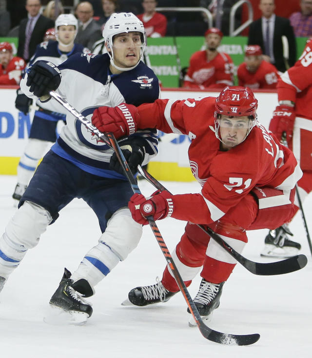 Winnipeg Jets left wing Brandon Tanev, left, battles for position with Detroit Red Wings center Dylan Larkin (71) during the first period of an NHL hockey game Friday, Oct. 26, 2018, in Detroit. (AP Photo/Duane Burleson)