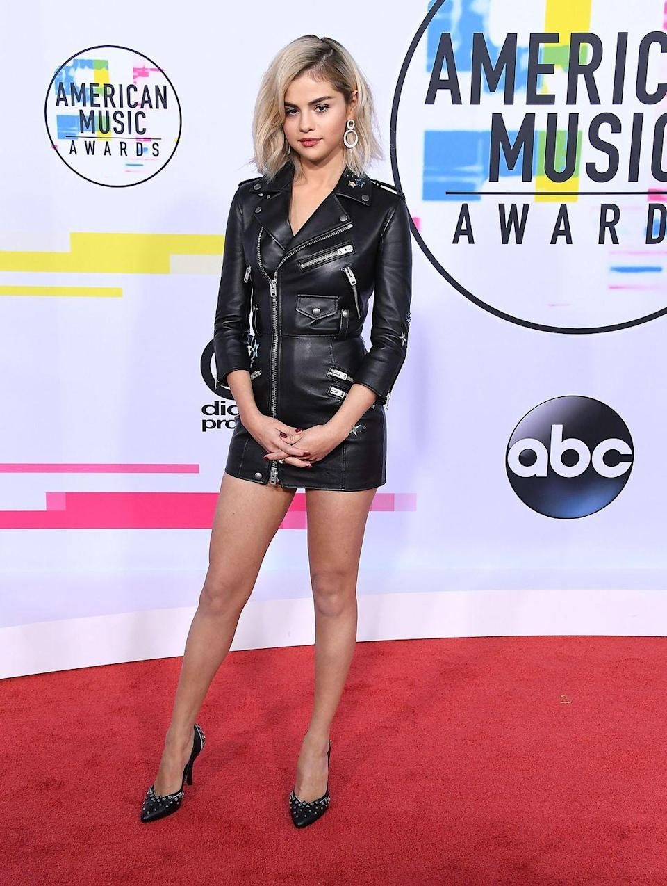 <p>Selena Gomez wore a black leather Coach dress on the AMA Awards red carpet in Los Angeles, November 2017</p>