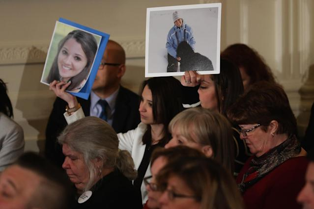 WASHINGTON, DC - JANUARY 05: Guests hold up images of victims of gun violence as U.S. President Barack Obama delivers remarks about his efforts to increase federal gun control in the East Room of the White House January 5, 2016 in Washington, DC. Without approval from Congress, Obama is sidestepping the legislative process with executive actions to expand background checks for some firearm purchases and step up federal enforcement of existing gun laws. (Photo by Chip Somodevilla/Getty Images)