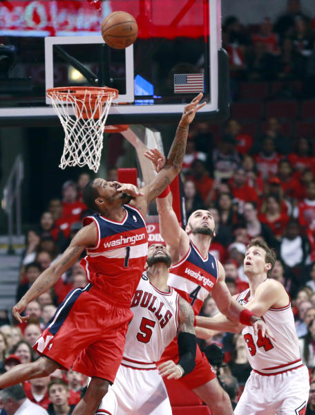 Washington Wizards forward Trevor Ariza (1), Chicago Bulls forward Carlos Boozer (5), Marcin Gortat (4) and Mike Dunleavy (34), battle for a rebound during the first half of Game 5 in an opening-round NBA basketball playoff series Tuesday, April 29, 2014, in Chicago. (AP Photo/Charles Rex Arbogast)