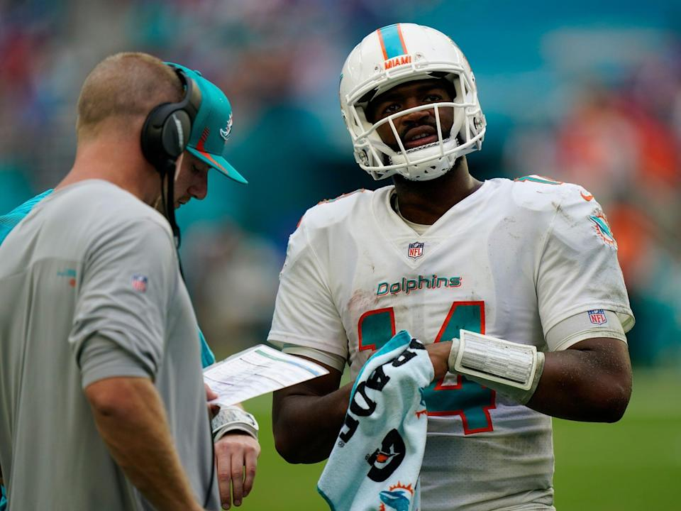 Jacoby Brissett talks over things with Dolphins staff on the sideline.