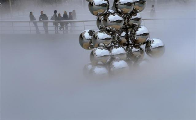"""Schoolchildren look at Anish Kapoor's """"Tall Tree And The Eye"""" through fog created by Japanese artist Fujiko Nakama's """"Fog"""" at the Guggenheim Museum in the Spanish Basque city of Bilbao January 12, 2011."""