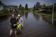 A father and son walk through their flooded street, in the town of Brommelen, Netherlands, Saturday, July 17, 2021. In the southern Dutch province of Limburg, which also has been hit hard by flooding, troops piled sandbags to strengthen a 1.1-kilometer (0.7 mile) stretch of dike along the Maas River, and police helped evacuate low-lying neighborhoods. (AP Photo/Bram Janssen)