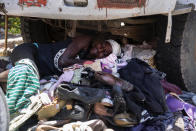 A vendor of used shoes and secondhand clothing sleeps under a truck in Port-au-Prince, Haiti, Saturday, July 10, 2021, three days after President Jovenel Moise was assassinated in his home. (AP Photo/Joseph Odelyn)