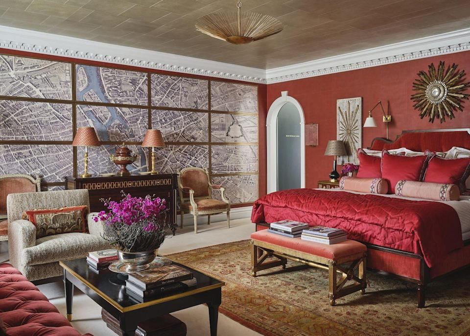"""<p><a href=""""https://www.alexahampton.com/"""" rel=""""nofollow noopener"""" target=""""_blank"""" data-ylk=""""slk:Alexa Hampton"""" class=""""link rapid-noclick-resp"""">Alexa Hampton</a>'s inspiration for the home's primary bedroom came from the association many design enthusiasts have with her father's iconic red rooms. The designer realized she hadn't designed a truly red room in years and wanted to challenge the notion that you can't do a red bedroom by showing how to create one in an elegant, balanced way. Her first call was to Hyde Park Moldings to zhush up the current moldings, recase the door frames, and build bookcases into the walls, all in a gleaming white.</p><p>""""With all the red being used here, a white tonic is important for all the richness—it acts like a palate cleanser,"""" says Hampton. The humble, light ticking stripe fabric from my collection with Eastern Accents that's used in the bedding and under curtains is like 'the little engine that could' here.""""</p><p>Everywhere you turn in this space, there is a delicious moment of contrast that balances light with dark, ticking stripes with velvet, and plush with plaster. Each vignette also feels impeccably collected, and the star of the show (if we must choose) is the stunning maps Hampton created with Gracie as part of a new digitized collection that covers an entire wall and further balances the bold space. Yet, as much as this room is beautiful to look at, it feels far from museum-like, inviting all who long to see the collected pieces between its four red walls.</p><p>""""There are 12 seats in the room excluding the bed, and I love it's coziness and the way we use bedrooms now,"""" says Hampton. """"That's how I use my own bedroom—my kids come in and surround me and chat—so I think it's a real luxury to be able to cozy up comfortably with everyone in there.""""</p>"""
