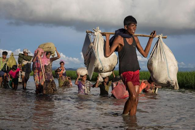 <p>Thousands of Rohingya refugees fleeing from Myanmar walk along a muddy rice field after crossing the border in Palang Khali, Cox's Bazar, Bangladesh, on October 9, 2017. (Photograph by Paula Bronstein/Getty Images) </p>