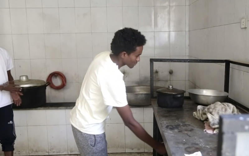 In this Wednesday, July 17, 2019 frame grab from video, Ahmed Saleh Ibrahim, a 19-year-old Sudanese, who made his way into Libya with the help of smugglers last year prepares food in a migrant detention center in the city of Sabha, which is about 650 kilometers, or 400 miles, south of the capital, Tripoli, Libya. (AP Photo)
