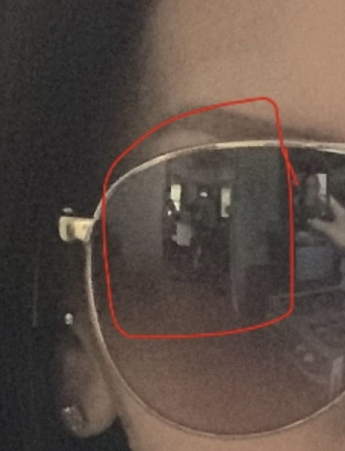 The woman's sunglasses reflection with a red circle around the two boys. Source: Quora