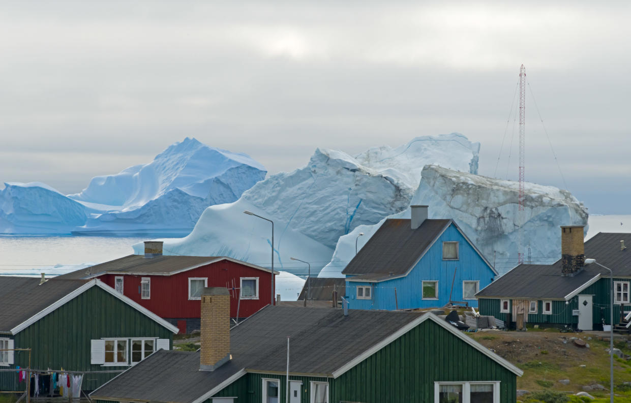 Brightly painted houses with floating iceberg, Qeqertarsuaq, Greenland