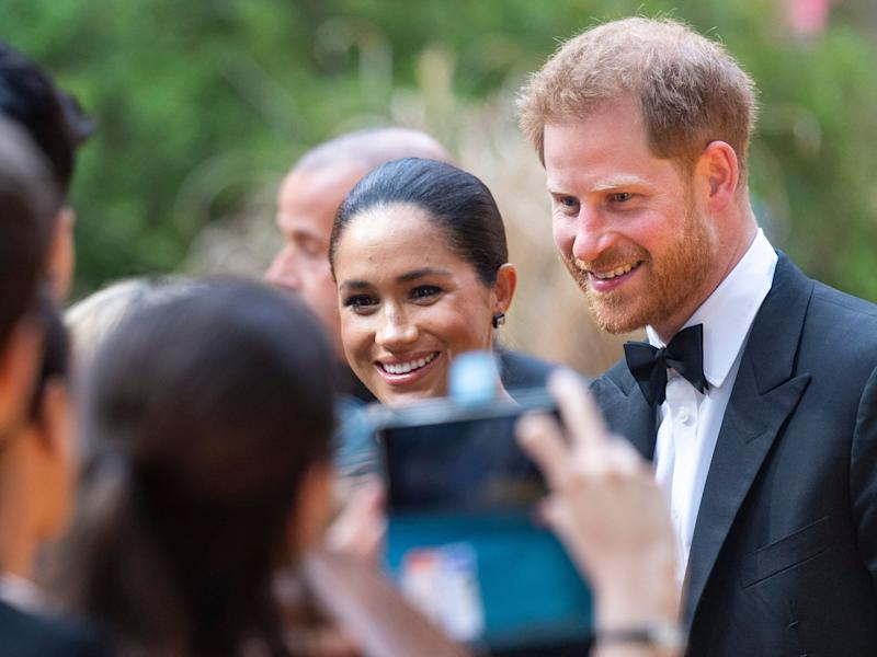 "A fan snaps a photo of Meghan and Harry at the London premiere of ""The Lion King"" on July 14. (Photo: Mark Cuthbert via Getty Images)"