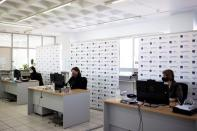 Employees of the State Independent Authority of Public Revenue speak to citizens via teleconference in Athens