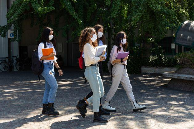 Students wearing protective face masks walking out from school (Photo: LeoPatrizi via Getty Images)