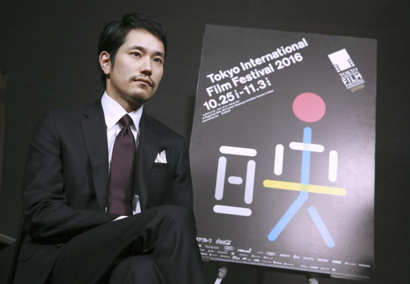 In this Nov. 2, 2016 photo, Japanese actor Kenichi Matsuyama sits next to a banner of Tokyo International Film Festival during an interview in Tokyo. The devotion Matsuyama gave to portraying a shogi prodigy who lived a fearlessly single-minded life is clear in the months he spent practicing placing the pawns in the Japanese board game, immersing himself in the master's selfless view on death and gorging to gain weight. (AP Photo/Eugene Hoshiko)