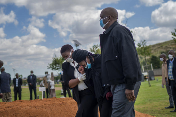 FILE - In this April 16, 2020, file photo, relatives grieve Benedict Somi Vilakasi, a Soweto coffee shop manager who died of COVID-19, at his burial ceremony at the Nasrec Memorial Park outside Johannesburg, South Africa. Africa has surpassed 100,000 confirmed deaths from COVID-19 as the continent praised for its early response to the pandemic now struggles with a dangerous resurgence and medical oxygen often runs desperately short. (AP Photo/Jerome Delay, File)