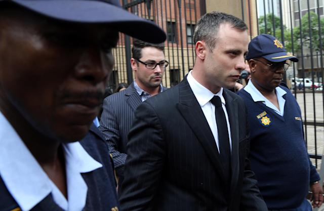 Oscar Pistorius, middle, accompanied by brother Carl Pistorius, behind, and police officers leaves the high court in Pretoria, South Africa, Wednesday, April 16, 2014. Pistorius is charged with murder for the shooting death of his girlfriend, Reeva Steenkamp, on Valentines Day in 2013. (AP Photo/Themba Hadebe)
