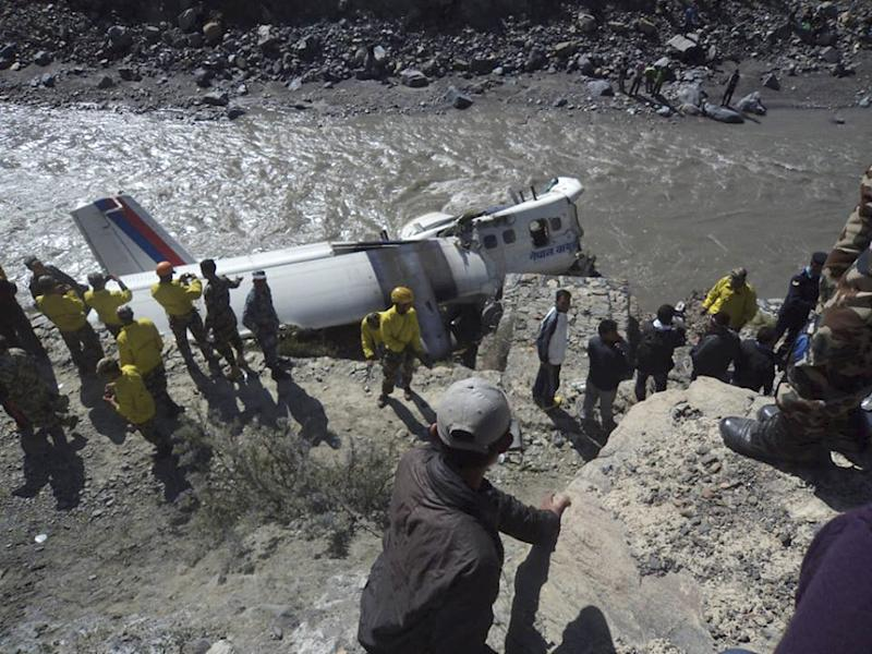 Nepalese rescuers and other people stand near the wreckage of a Nepal Airlines plane that crashed on the banks of Kaligandaki river at Jomsom, some 200 kilometers (125 miles) northwest of Katmandu, Nepal, Thursday, May 16, 2013. The plane crashed while trying to land at Jomsom airport in northern Nepal early Thursday, injuring all 21 people on board. No one was killed. (AP Photo/Ananda Subedi)