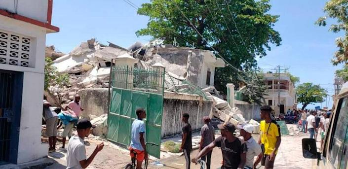 People stand outside the residence of the Catholic bishop after it was damaged by an earthquake in Les Cayes, Haiti, Saturday, Aug. 14, 2021.