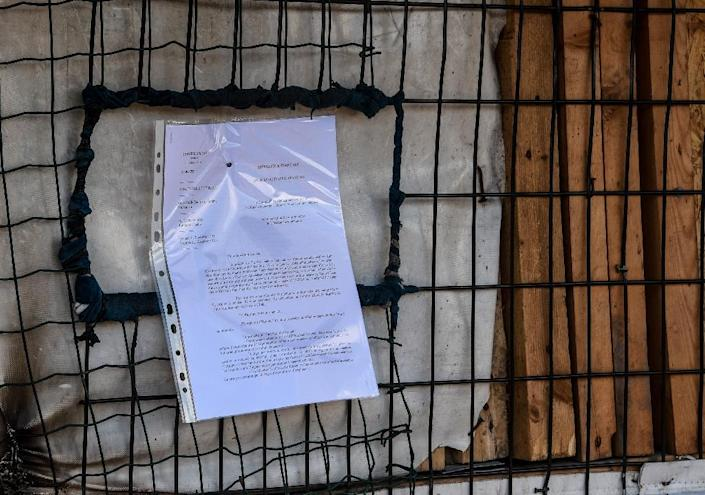 """This photo taken on October 17, 2016 shows an eviction letter posted by French government authorities calling for the evacuation of the """"Jungle"""" migrant and refugee encampment in Calais before dismantlement of the site (AFP Photo/Denis Charlet)"""