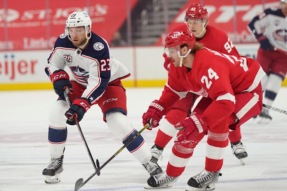 Columbus Blue Jackets left wing Stefan Matteau (23) and Detroit Red Wings defenseman Jon Merrill (24) chase the puck during the first period of an NHL hockey game, Saturday, March 27, 2021, in Detroit.