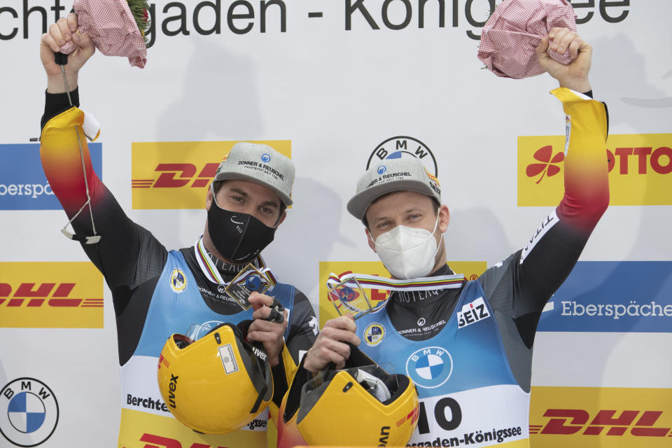 Tobias Wendl, left, and Tobias Arlt of Germany present their medals in the finish area after the men's doubles race at the Luge World Championships in Koenigssee,Germany, Friday, Jan. 29, 2021. (AP Photo/Andreas Schaad)