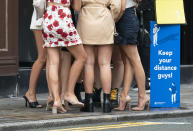 FILE - In this file photo dated Saturday July 4, 2020, women are seen outside a bar in Manchester, England, as England eases lockdown restrictions for pubs and restaurants to reopen for the first time, while asking for people to continue social restrictions. The British government insists that science is guiding its decisions as the country navigates its way through the coronavirus pandemic. But a self-appointed group of independent experts led by a former government chief adviser says it sees little evidence-based about Britain's response. Unlike other countries, the scientific opposition to Britain's approach is remarkably organized. The independent group sits almost in parallel to the government's own scientists, assesses the same outbreak indicators and has put out detailed reports on issues such contact tracing, reopening schools and pubs, and relaxing social distancing(AP Photo/Jon Super, File)
