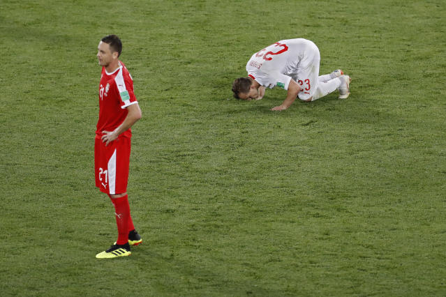 Switzerland's Xherdan Shaqiri, right, kisses the pitch next to Serbia's Nemanja Matic after scoring his side's second goal during the group E match between Switzerland and Serbia at the 2018 soccer World Cup in the Kaliningrad Stadium in Kaliningrad, Russia, Friday, June 22, 2018. Shaqiri scored once in Switzerland's 2-1 victory. (AP Photo/Antonio Calanni)