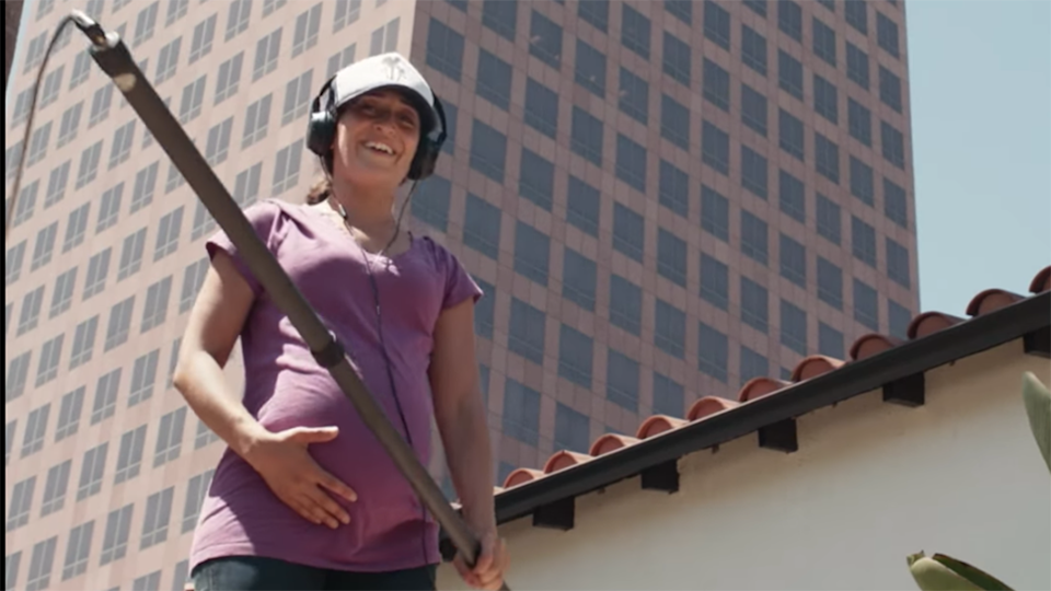 Pregnant woman hold belly while operating boom mic on Netflix Motherhood in Focus series