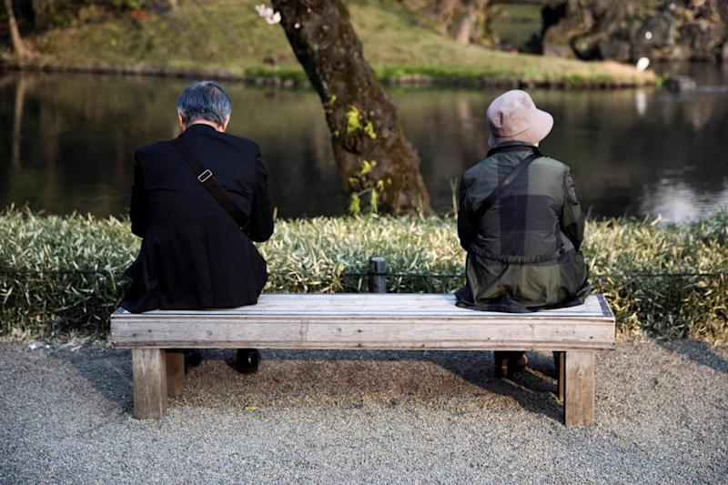 An elderly man and woman sit on a bench in a park in Tokyo (AFP/Getty Images)