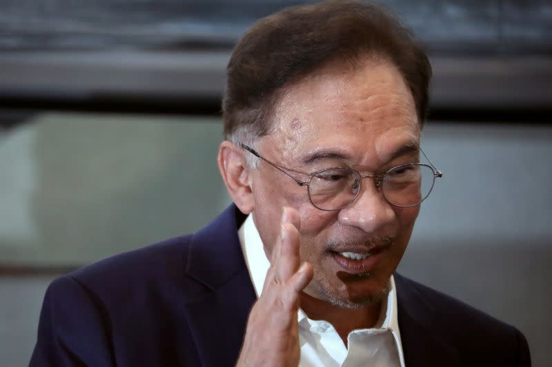 FILE PHOTO: Malaysia opposition leader Anwar Ibrahim waves after a news conference in Kuala Lumpur