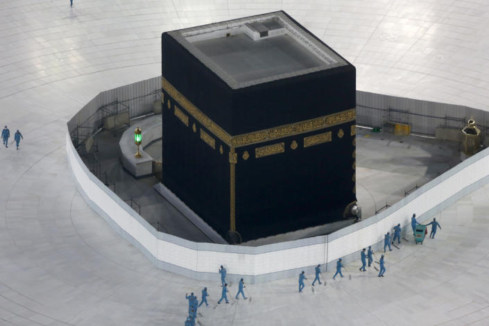"""FILE - In this March 7, 2020 file photo, workers disinfect the ground around the Kaaba, the cubic building at the Grand Mosque, in the Muslim holy city of Mecca, Saudi Arabia after authorities emptied Islam's holiest site for sterilization over fears of the new coronavirus. Saudi Arabia said Tuesday, June 22, 2020 this year's hajj will not be canceled, but that due to the coronavirus only """"very limited numbers"""" of people will be allowed to perform the pilgrimage that traditionally draws around 2 million people from around the world to Mecca once a year. (AP Photo/Amr Nabil, File)"""