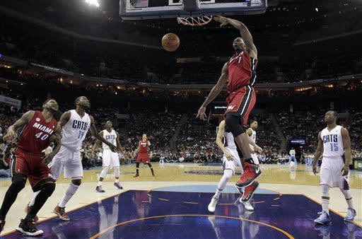 Miami Heat's Chris Bosh (1) gets free for a dunk against the Charlotte Bobcats during the first half of an NBA basketball game in Charlotte, N.C., Friday, April 5, 2013. (AP Photo/Bob Leverone)