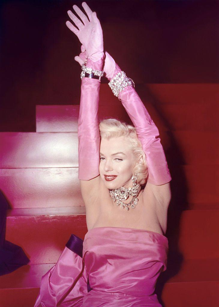 """<p>One of Marilyn Monroe's most famous looks (of many) was in <em>Gentlemen Prefer Blondes</em>. During her rendition of """"Diamonds Are a Girl's Best Friend,"""" the actress—dripping in diamonds, of course—rocked a hot-pink strapless evening gown with matching gloves.</p>"""
