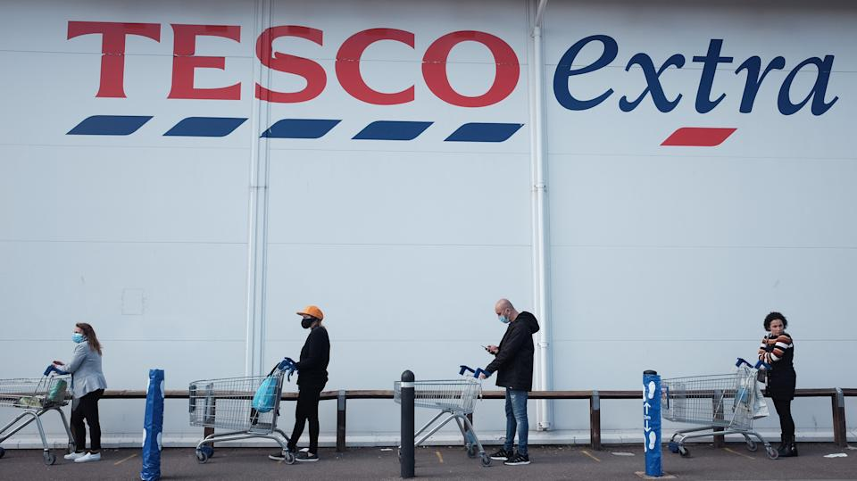 People practice social distancing while queuing outside a Tesco Extra store in Twickenham, London, as the UK continues in lockdown to help curb the spread of the coronavirus.