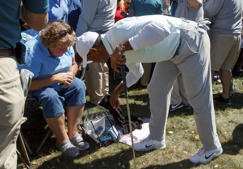 Tiger Woods reaches in to a fan's bag after his approach shot on the ninth hole landed in it during the second round of the Valspar Championship golf tournament Friday, March 9, 2018, in Palm Harbor, Fla. (AP Photo/Mike Carlson)