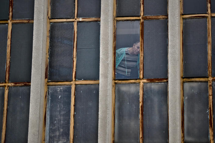 """FILE - In this Sunday, Oct. 30, 2016, file photograph a man watches from a hospital a silent march in memory of those who died a year ago at the Colectiv nightclub in Bucharest, Romania. The Oscar-nominated Romanian documentary film """"Collective"""" follows a group of journalists delving into the state of health care in the eastern European country in the wake of a deadly 2015 nightclub fire that left dozens of burned victims in need of complex treatment. What they revealed was decades of deep-rooted corruption, a heavily politicized system scarily lacking in care. (AP Photo/Vadim Ghirda, File)"""