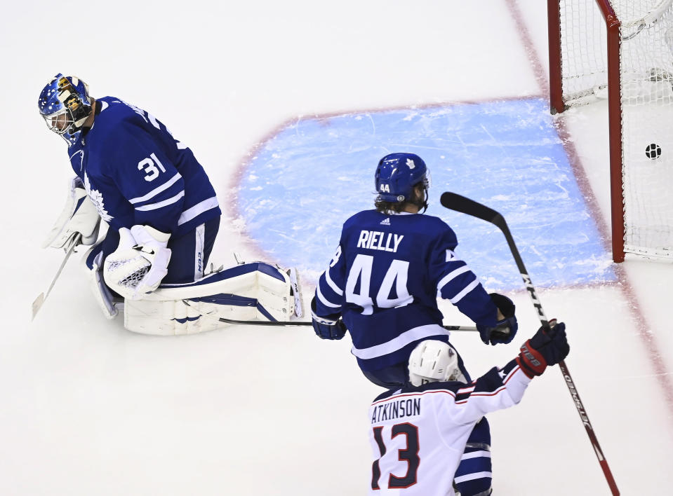 Columbus Blue Jackets right wing Cam Atkinson (13) scores past Toronto Maple Leafs goaltender Frederik Andersen (31) as Leafs defenceman Morgan Rielly (44) watches during the third period of an NHL hockey playoff game in Toronto, Sunday, Aug. 2, 2020. (Nathan Denette/The Canadian Press via AP)