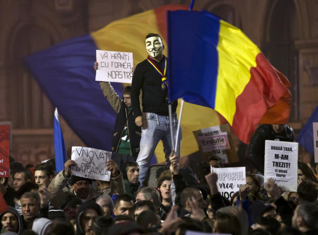A man wearing a Guy Fawkes mask stands above protesters shouting slogans against the Romanian politicians during the fourth day of protests, joined by tens of thousands across the country, calling for early elections, in Bucharest, Romania, Friday, Nov. 6, 2015. (AP Photo/Vadim Ghirda)