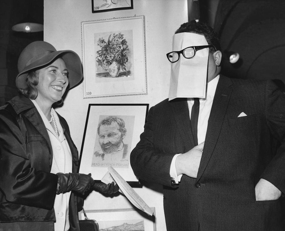 Harry Secombe (1921 - 2001), a member of the comedy team the 'Goons', hiding his face behind a piece of paper while singer Vera Lynn looks on. (Photo by Central Press/Getty Images)