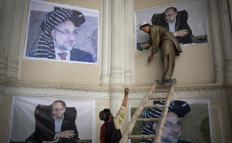 Afghan men hang posters of slain Afghan governor Arsallah Jamal on the walls of the Eid Gha mosque in Kabul, Afghanistan, Thursday, Oct 17, 2013. Afghan officials, dignitaries and family members attended the funeral of the governor of eastern Logar province, who was killed in an insurgent attack earlier this week. (AP Photo/Anja Niedringhaus)