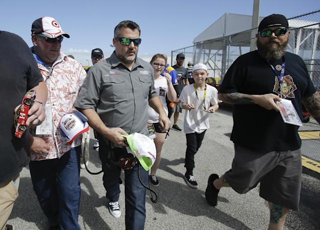 "Car owner <a class=""link rapid-noclick-resp"" href=""/nascar/sprint/drivers/87/"" data-ylk=""slk:Tony Stewart"">Tony Stewart</a>, center, is surrounded by fans seeking autographs as he walks through the garages at a NASCAR auto racing practice session at Daytona International Speedway, Friday, Feb. 24, 2017, in Daytona Beach, Fla. (AP Photo/John Raoux)"
