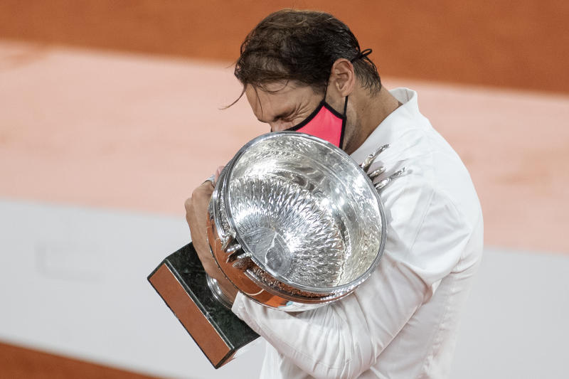 Rafael Nadal reacts as he embraces the trophy after his victory against Novak Djokovic in the Singles Final on Court Philippe-Chatrier during the French Open.